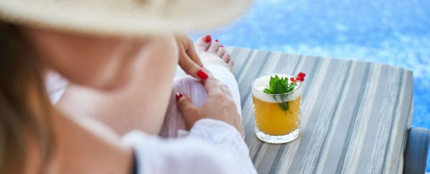 Lady with holiday drink by the pool