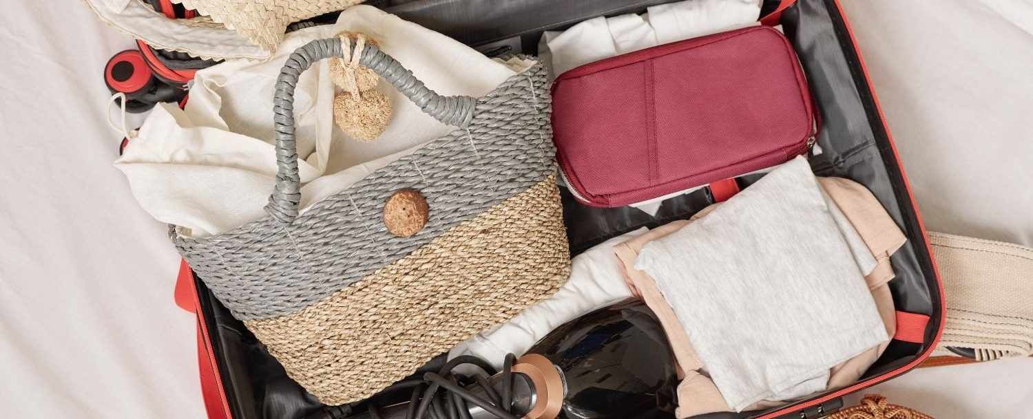 Packed bag with summer essentials like a sunhat.